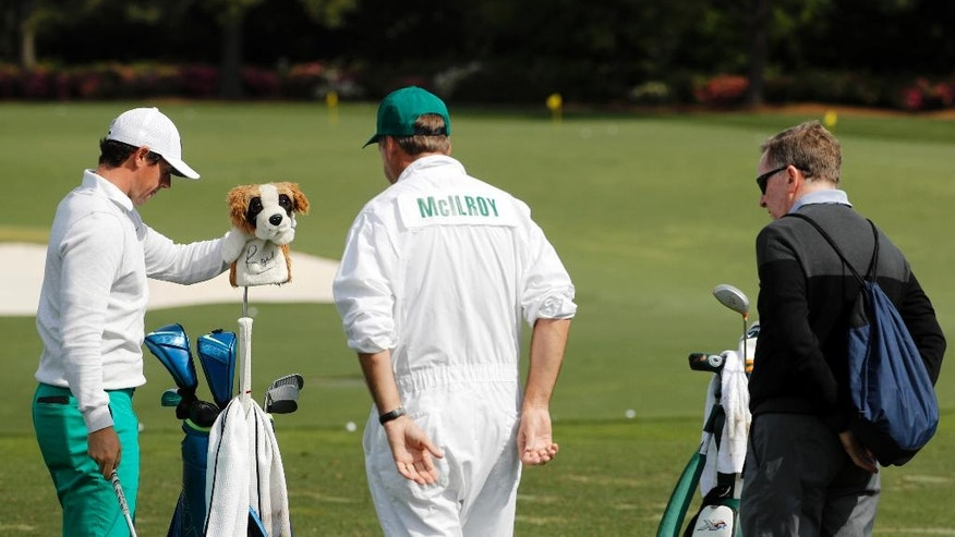 Coach Michael Bannon, right and caddie Jean-Paul Fitzgerald watch as Rory McIlroy, of Northern Ireland, prepares to hit on the driving range during a practice round for the Masters golf tournament Wednesday, April 6, 2016, in Augusta, Ga. (AP Photo/Chris Carlson)