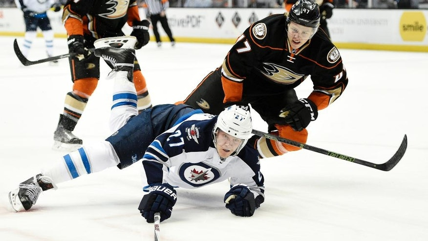 Winnipeg Jets right wing Nikolaj Ehlers, front, of Denmark, lunges for the puck as he falls to the ice while under pressure by Anaheim Ducks defenseman Hampus Lindholm, top, of Sweden, during the first period of an NHL hockey game in Anaheim, Calif., Tuesday, April 5, 2016. (AP Photo/Kelvin Kuo)
