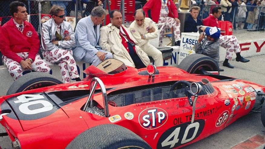 FILE - In this May 31, 1967, file photo, team owner Andy Granatelli, in trench coat, sits with crew members beside the STP-Paxton turbine powered car of Parnelli Jones before the 51st running of the Indianapolis 500 auto race at Indianapolis Motor Speedway in Indianapolis, Ind. Jones dominated the race until a transmission problem with three laps to go. A.J. Foyt won the race. (AP Photo/File)