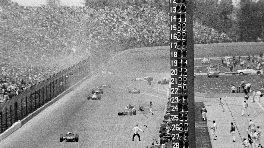 FILE - In this May 31, 1967, file photo, AJ Foyt, foreground left, drives his Coyote Ford past the checkered flag after avoiding a multi-car wreck on the last lap to win the Indianapolis 500 auto race at Indianapolis Motor Speedway in Indianapolis, Ind. (AP Photo/File)