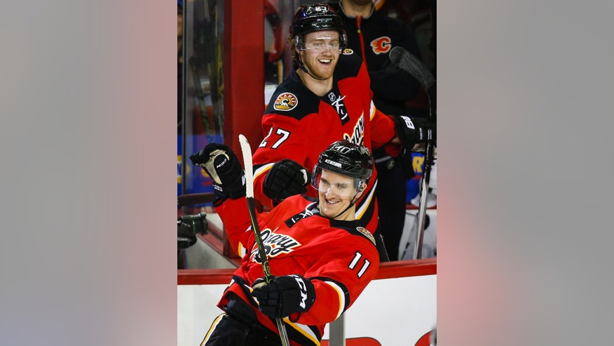 Calgary Flames' Mikael Backlund, right, from Sweden, is congratulated on his hat trick by teammate Dougie Hamilton during the second period of an NHL hockey game against the Vancouver Canucks on Thursday, April 7, 2016, in Calgary, Alberta. (Jeff McIntosh/The Canadian Press via AP)