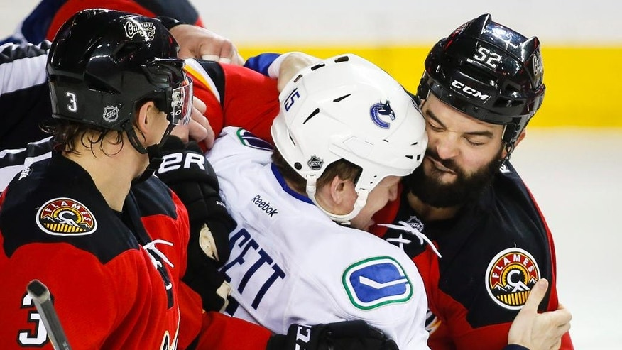 Vancouver Canucks' Derek Dorsett, center, fights with Calgary Flames' Brandon Bollig (52) during the first period of an NHL hockey game Thursday, April 7, 2016, in Calgary, Alberta. (Jeff McIntosh/The Canadian Press via AP)