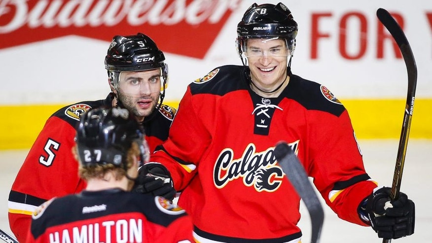 Calgary Flames' Joe Colborne, right, celebrates his goal with teammates Dougie Hamilton, front left, and Mark Giordano during the second period of an NHL hockey game against the Vancouver Canucks on Thursday, April 7, 2016, in Calgary, Alberta. (Jeff McIntosh/The Canadian Press via AP)
