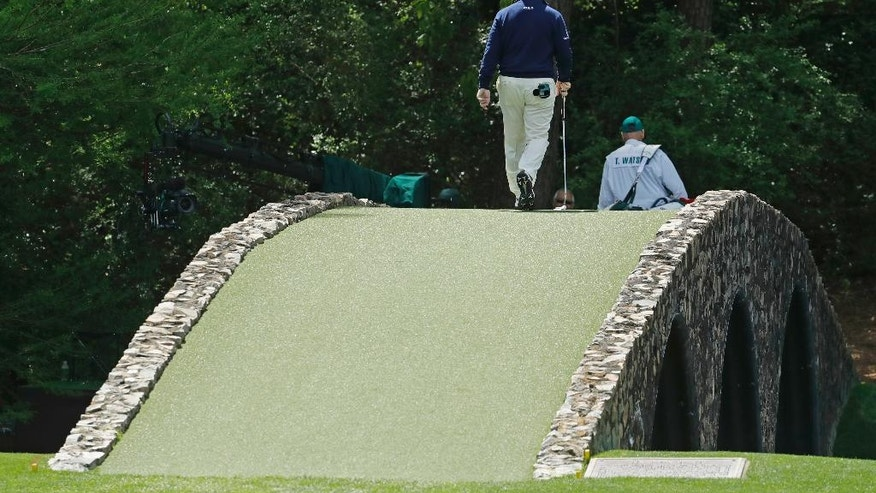 Tom Watson walks over the Hogan Bridge during the first round of the Masters golf tournament Thursday, April 7, 2016, in Augusta, Ga. (AP Photo/Charlie Riedel)