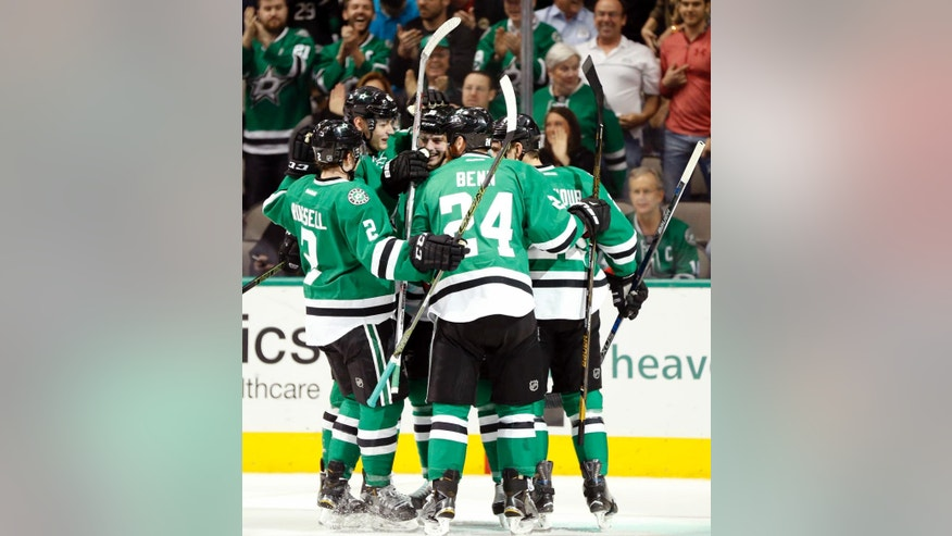 Dallas Stars center Jason Dickinson, center, celebrates his goal with teammates, including defensemen Jordie Benn (24) and Kris Russell (2),  during the first period of an NHL hockey game against the Colorado Avalanche, Thursday, April 7, 2016, in Dallas. (AP Photo/Jim Cowsert)