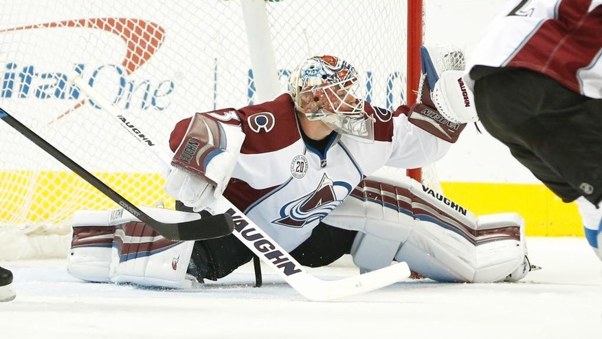 Colorado Avalanche goalie Calvin Pickard (31) makes a glove-save on a shot on goal-attempt by the Dallas Stars during the first period of an NHL hockey game, Thursday, April 7, 2016, in Dallas. (AP Photo/Jim Cowsert)