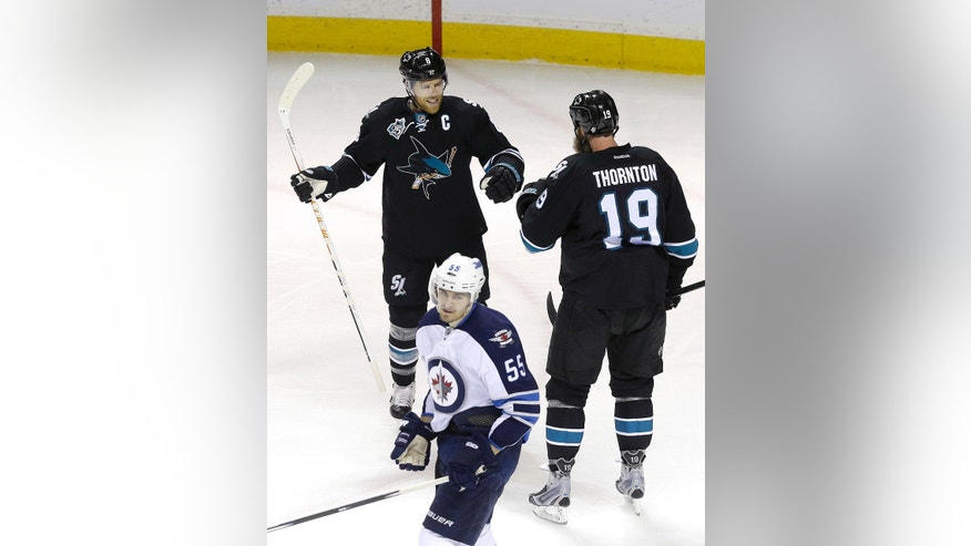 San Jose Sharks' Joe Pavelski, left, and Joe Thornton (19) celebrate after Pavelski scored during the first period of an NHL hockey game against the Winnipeg Jets in San Jose, Calif., Thursday, April 7, 2016. Jets' Mark Scheifele (55) looks on. (AP Photo/Jeff Chiu)