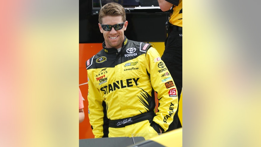 Carl Edwards smiles before qualifying for  the NASCAR Sprint Cup Series auto race at Texas Motor Speedway in Fort Worth, Texas, Friday, April 8, 2016. (AP Photo/Ralph Lauer)