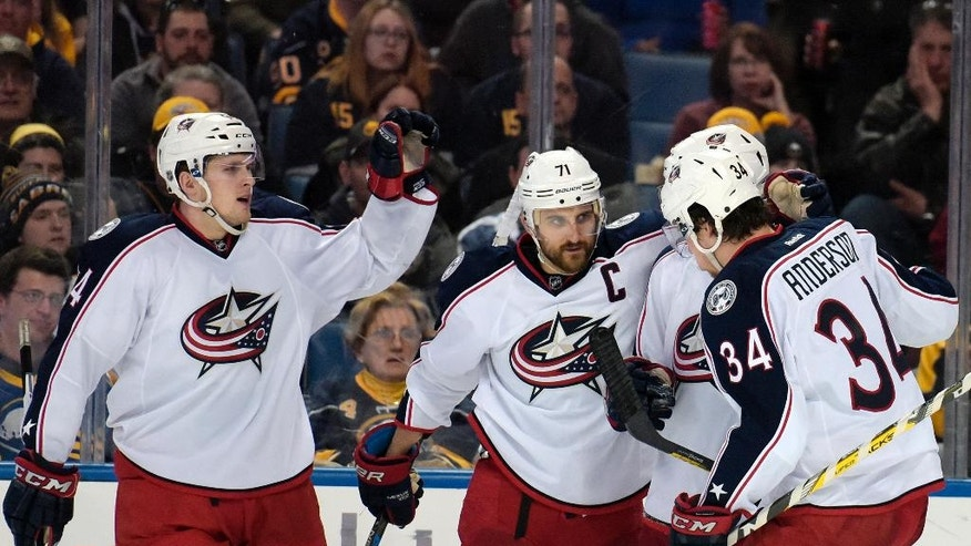 Columbus Blue Jackets' Justin Falk, right, Nick Foligno (71) and Josh Anderson (34) celebrate a goal by Foligno during the second period of an NHL hockey game against the Buffalo Sabres, Friday, April 8, 2016, in Buffalo, N.Y. (AP Photo/Gary Wiepert)