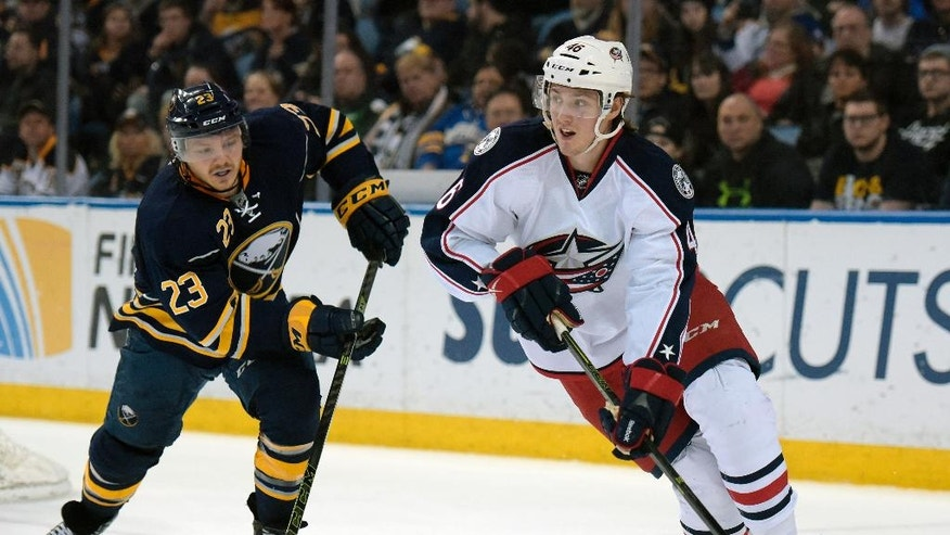Buffalo Sabres center Sam Reinhart (23) pursues as Columbus Blue Jackets defenseman Dean Kukan (46), of the Czech Republic, looks to pass the puck up ice during the first period of an NHL hockey game, Friday, April 8, 2016, in Buffalo, N.Y. (AP Photo/Gary Wiepert)