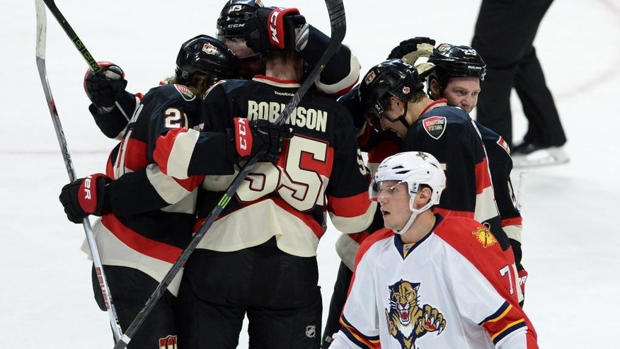 Florida Panthers defenseman Dmitry Kulikov, makes his way to the bench as Ottawa Senators right wing Buddy Robinson celebrates his first NHL goal with teammates during the second period of an NHL hockey game, Thursday, April 7, 2016 in Ottawa, Ontario. (Sean Kilpatrick/The Canadian Press via AP) MANDATORY CREDIT