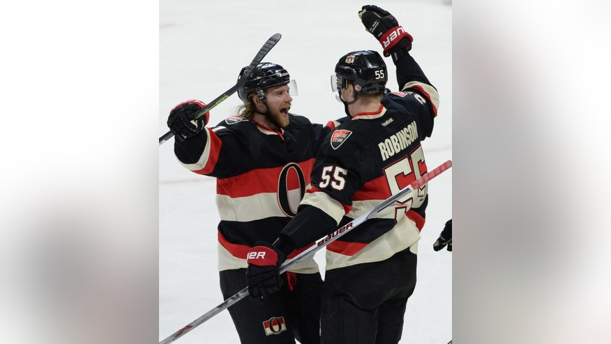 Ottawa Senators right wing Buddy Robinson , right, celebrates his first NHL goal with teammate Ottawa Senators defenseman Michael Kostka during the second period of an NHL hockey game, Thursday, April 7, 2016 in Ottawa, Ontario. (Sean Kilpatrick/The Canadian Press via AP) MANDATORY CREDIT