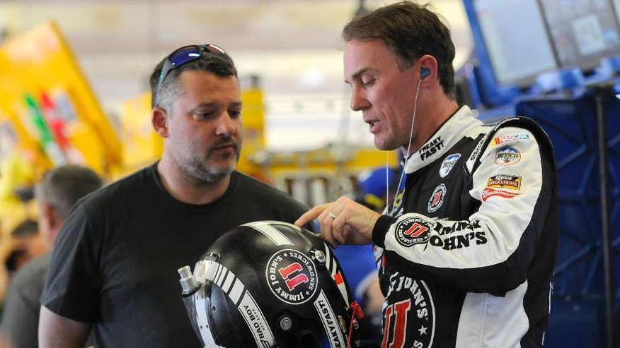 Kevin Harvick, right, talks with Tony Stewart during NASCAR Sprint Cup Series auto race practice at Texas Motor Speedway in Fort Worth, Texas, Thursday, April 7, 2016. The annual Duck Commander 500 runs Saturday night. (AP Photo/Ralph Lauer)