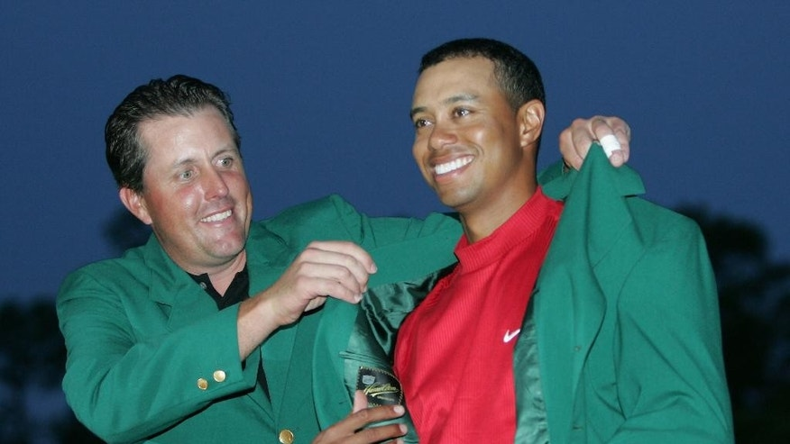FILE - In this April 10, 2005, file photo, Tiger Woods, right, gets help with his green jacket from Phil Mickelson, left, after winning the Masters at Augusta National Golf Club in Augusta, Ga. The first tee on the opening day of the Masters might be the closest thing to a living, breathing interactive Hall of Fame exhibit in sports. Past Masters champions are invited to strike a ceremonial opening tee shot each year. Don't worry about a drop-off in quality anytime soon, either. Still in the pipeline are Tom Watson, Nick Faldo, Mickelson and Woods.(AP Photo/Morry Gash, File)