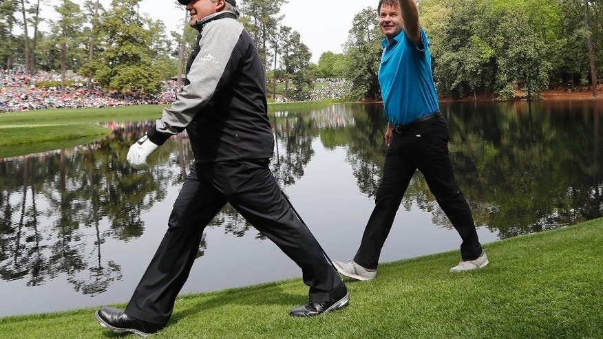 Angel Cabrera, of Argentina, and Nick Faldo walk to the ninth hole during the par three competition at the Masters golf tournament Wednesday, April 6, 2016, in Augusta, Ga. (AP Photo/David J. Phillip)