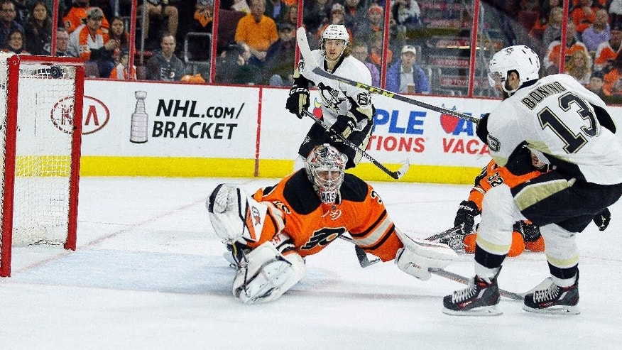 Pittsburgh Penguins' Nick Bonino, right, scores past Philadelphia Flyers' Steve Mason during the first period of an NHL hockey game Saturday, April 9, 2016 in Philadelphia. (AP Photo/Tom Mihalek)