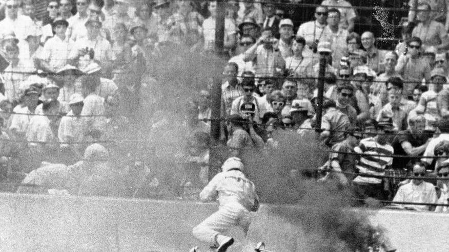 FILE - In this May 30, 1969, file photo, Jim McElreath, of Arlington, Texas, leaps from his burning racer on the homestretch during the 53rd running of the Indianapolis 500 auto race at Indianapolis Motor Speedway Indianapolis, Ind.  (AP Photo)