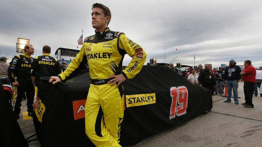 Carl Edwards stands by his covered car as a light rain falls before the NASCAR Sprint Cup Series auto race at Texas Motor Speedway in Fort Worth, Texas, Saturday, April 9, 2016. (AP Photo/Tim Sharp)