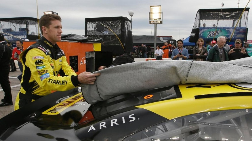 Carl Edwards uncovers his car after a light rain stopped falling, before the NASCAR Sprint Cup Series auto race at Texas Motor Speedway in Fort Worth, Texas, Saturday, April 9, 2016. (AP Photo/Tim Sharp)