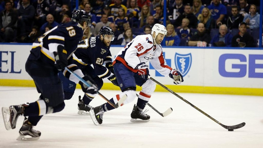 Washington Capitals' Daniel Winnik (26) skates downice as St. Louis Blues' Jay Bouwmeester (19) and Alex Pietrangelo give chase during the first period of an NHL hockey game Saturday, April 9, 2016, in St. Louis. (AP Photo/Jeff Roberson)