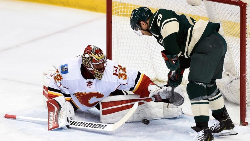 Calgary Flames goalie Niklas Backstrom (32), of Finland, blocks a shot by Minnesota Wild right wing Jason Pominville (29) during the first period of an NHL hockey game Saturday, April 9, 2016, in St. Paul, Minn. (AP Photo/Hannah Foslien)