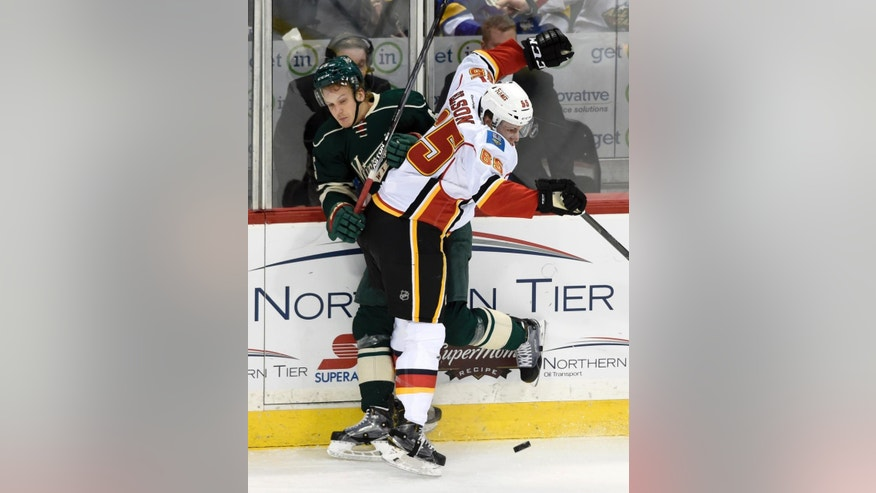 Calgary Flames' Turner Elson (65) checks Minnesota Wild's Jonas Brodin, of Sweden, during the first period of an NHL hockey game Saturday, April 9, 2016, in St. Paul, Minn. (AP Photo/Hannah Foslien)