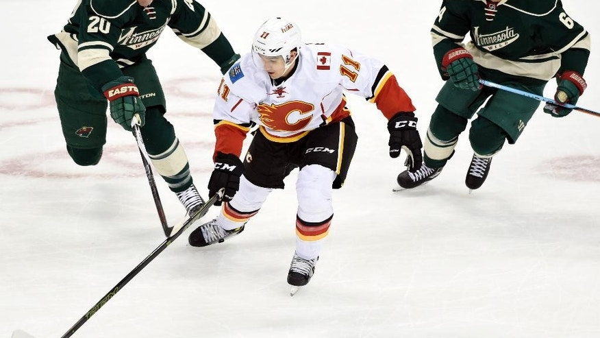 Calgary Flames' Mikael Backlund (11) handles the puck against Minnesota Wild's Ryan Suter (20) and Mikael Granlund (64) during the first period of an NHL hockey game Saturday, April 9, 2016, in St. Paul, Minn. (AP Photo/Hannah Foslien)