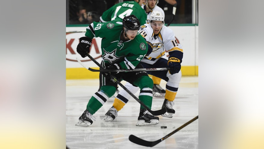 Dallas Stars center Cody Eakin (20) and Nashville Predators center Calle Jarnkrok (19) fight for the puck during the first period of an NHL hockey game on Saturday, April 9, 2016, in Dallas. (AP Photo/Michael Ainsworth)