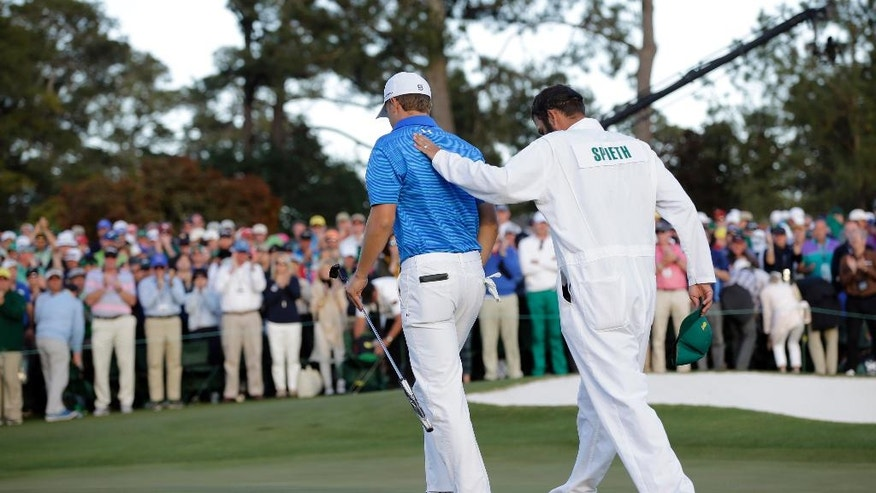 Jordan Spieth is consoled by his caddie Michael Greller on the 18th hole after the final round of the Masters golf tournament Sunday, April 10, 2016, in Augusta, Ga. (AP Photo/David J. Phillip)