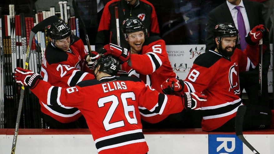 New Jersey Devils left wing Patrik Elias (26), of the Czech Republic, is mobbed by Damon Severson (28), Adam Larsson (5), of Sweden, and David Schlemko (8) after scoring a goal against the Toronto Maple Leafs during the third period of an NHL hockey game, Saturday, April 9, 2016, in Newark, N.J.  (AP Photo/Julio Cortez)