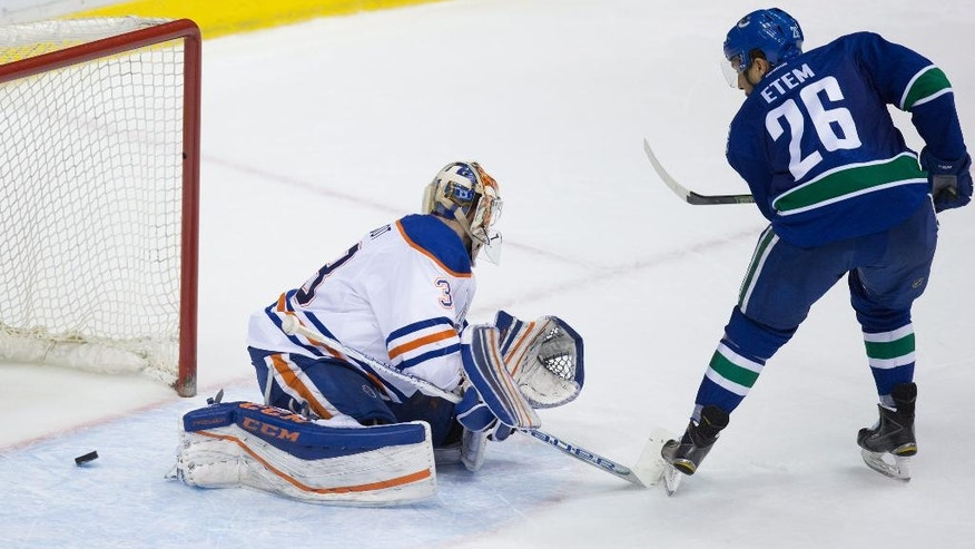 Vancouver Canucks' Emerson Etem, right, scores against Edmonton Oilers goalie Cam Talbot during the shootout in an NHL hockey game Saturday, April 9, 2016, in Vancouver, British Columbia. (Darryl Dyck/The Canadian Press via AP)