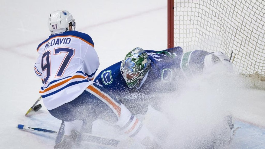 Edmonton Oilers' Connor McDavid, left, is stopped by Vancouver Canucks goalie Jacob Markstrom, of Sweden, during the shootout in an NHL hockey game Saturday, April 9, 2016, in Vancouver, British Columbia. (Darryl Dyck/The Canadian Press via AP)