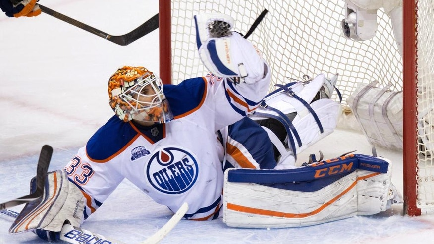 Edmonton Oilers' goalie Cam Talbot looks at the puck in his glove after stopping Vancouver Canucks' Daniel Sedin, not seen, during overtime of an NHL hockey game Saturday, April 9, 2016, in Vancouver, British Columbia. (Darryl Dyck/The Canadian Press via AP)