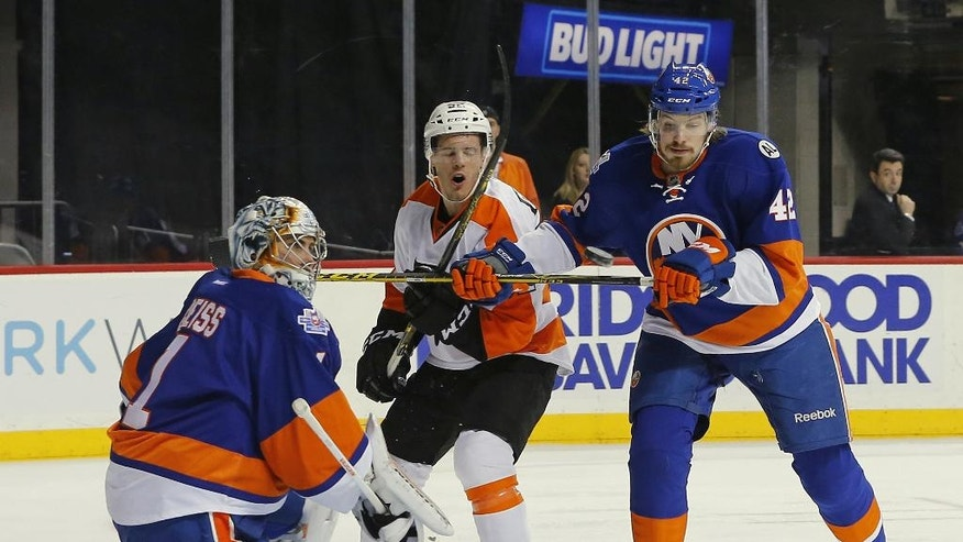 Philadelphia Flyers center Nick Cousins (52) and New York Islanders defenseman Scott Mayfield (42) attempts to control the airborne puck in front of Islander goalie Thomas Greiss (1) of Germany during the first period of an NHL hockey game in New York, Sunday, April 10, 2016. (AP Photo/Rich Schultz)