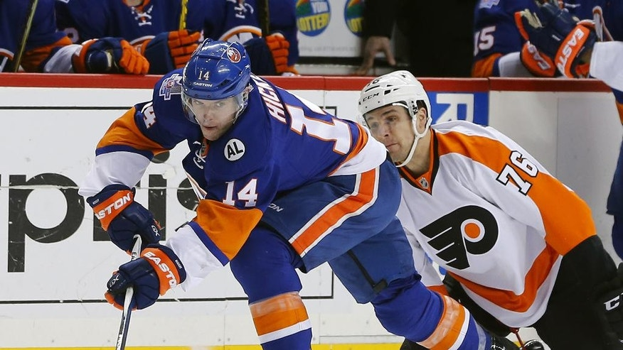 New York Islanders defenseman Thomas Hickey (14) moves the puck away from Philadelphia Flyers center Chris VandeVelde (76) during the first period of an NHL hockey game in New York, Sunday, April 10, 2016. (AP Photo/Rich Schultz)