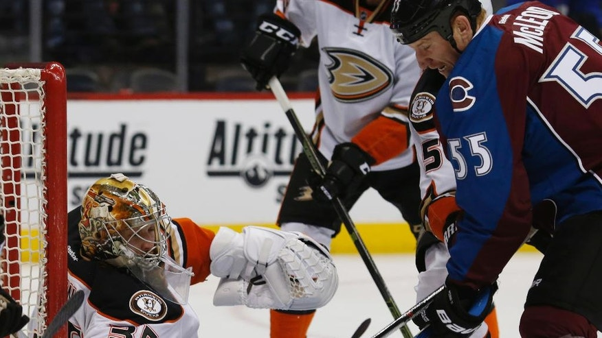Anaheim Ducks goalie John Gibson, left, makes a stick-save of a redirected shot off the stick of Colorado Avalanche left wing Cody McLeod (55) in the first period of an NHL hockey game Saturday, April 9, 2016, in Denver. (AP Photo/David Zalubowski)