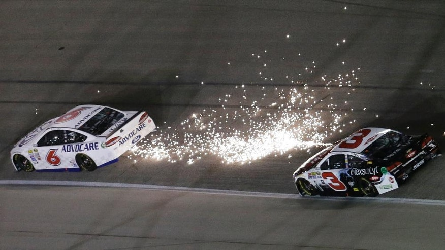 Trevor Bayne's car, left, showers sparks in front of Austin Dillon during the NASCAR Sprint Cup Series auto race at Texas Motor Speedway in Fort Worth, Texas, Saturday, April 9, 2016.(AP Photo/Tim Sharp)