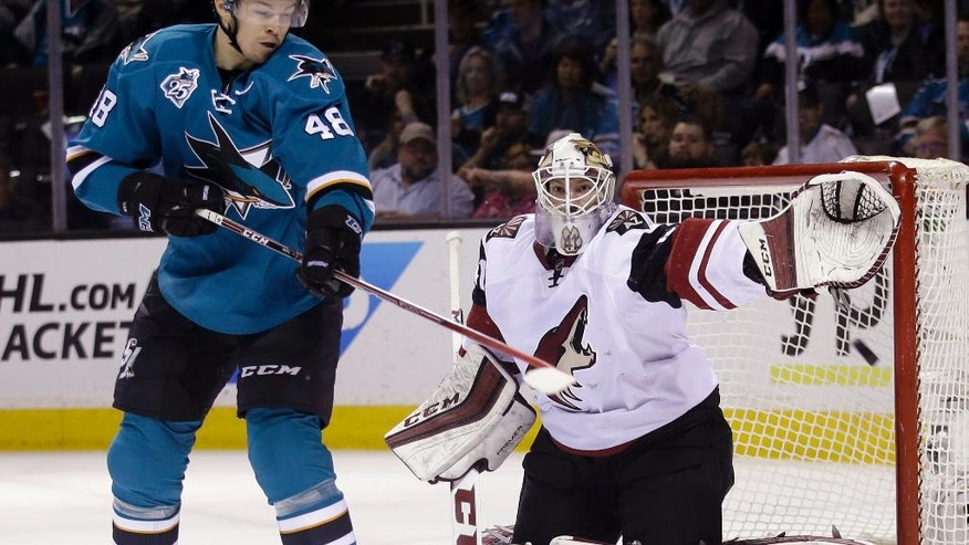 Arizona Coyotes goalie Mike Smith, right, deflects a shot in front of San Jose Sharks' Tomas Hertl (48) during the first period of an NHL hockey game Saturday, April 9, 2016, in San Jose, Calif. (AP Photo/Marcio Jose Sanchez)