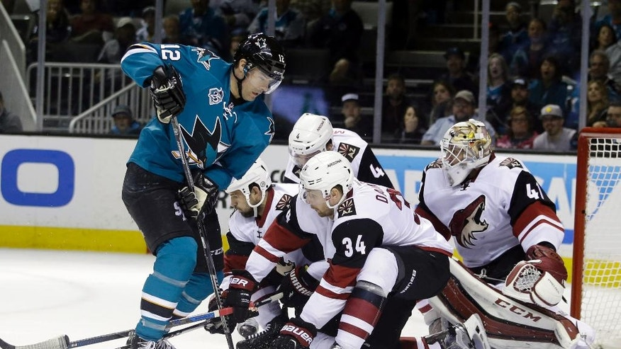 San Jose Sharks' Patrick Marleau (12) works in front of the goal against Arizona Coyotes' Klas Dahlbeck (34) and goalie Mike Smith (41) during the first period of an NHL hockey game Saturday, April 9, 2016, in San Jose, Calif. (AP Photo/Marcio Jose Sanchez)