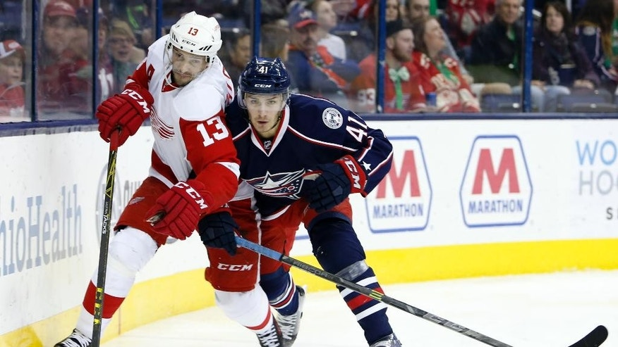 FILE - In this March 17, 2016, file photo, Detroit Red Wings' Pavel Datsyuk, left, of Russia, and Columbus Blue Jackets' Alexander Wennberg, of Sweden, chase a loose puck during the first period of an NHL hockey game in Columbus, Ohio. Datsyuk is expected to retire from the NHL after the playoffs. Datsyuk discussed his plans for the first time in an interview with the Detroit Free Press published Sunday, April 10, 2016. (AP Photo/Jay LaPrete, File)