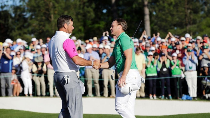 Danny Willett, right, of England, is congratulated by Lee Westwood, of England, on the 18th hole following his final round of the Masters golf tournament Sunday, April 10, 2016, in Augusta, Ga. (AP Photo/David J. Phillip)