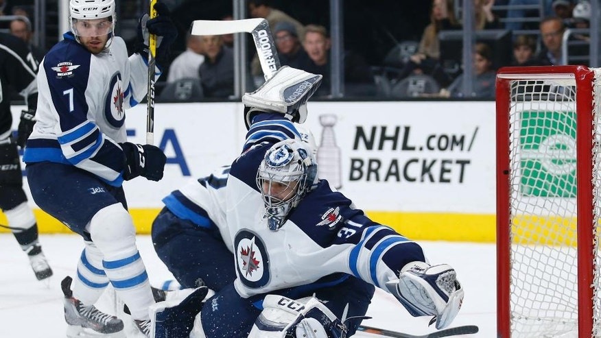 Winnipeg Jets goalie Ondrej Pavelec moves to make a save on a shot by Los Angeles Kings center Jeff Carter, not pictured, while Jets defenseman Ben Chiarot, left, defends during the second period of an NHL hockey game, Saturday, April 9, 2016, in Los Angeles. (AP Photo/Danny Moloshok)