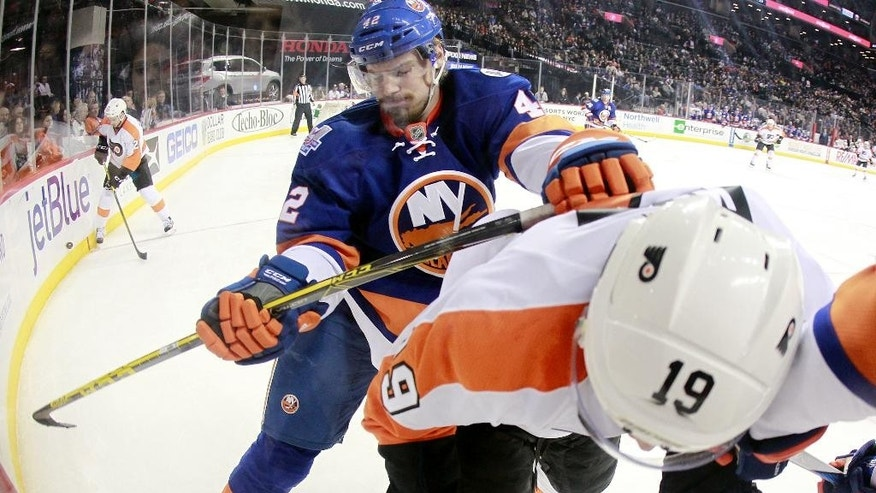 New York Islanders defenseman Scott Mayfield (42) checks Philadelphia Flyers center Jordan Weal (19) during the third period of an NHL hockey game in New York, Sunday, April 10, 2016. The Flyers defeated the Islanders 5-2. (AP Photo/Rich Schultz)
