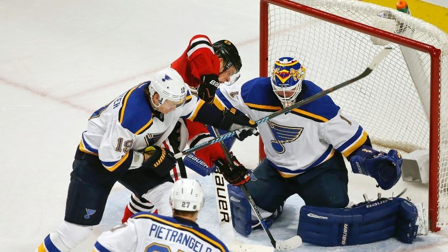 Chicago Blackhawks center Jonathan Toews, center, tries to score against St. Louis Blues goalie Brian Elliott, right, and defenseman Jay Bouwmeester, left, during the second period of an NHL hockey game Thursday, April 7, 2016, in Chicago. (AP Photo/Kamil Krzaczynski)