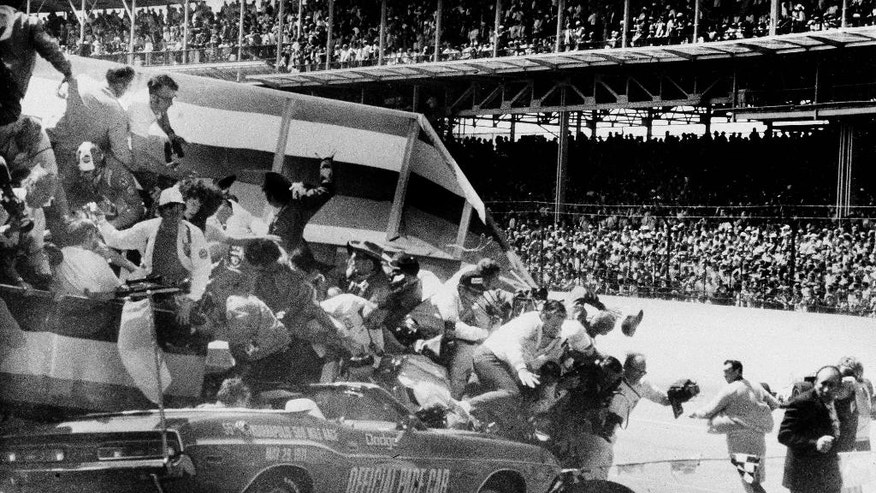 FILE - In this May 29, 1971, file photo, people fall off a camera stand after the stand was hit by the pace car driven by local Indianapolis-area Dodge dealer Eldon Palmer at the start of the Indianapolis 500 auto race at Indianaolis Motor Speedway in Indianapolis, Ind.  (Frank Hanes/Chicago Today via AP, File)  MANDATORY CREDIT CHICAGO TRIBUNE; CHICAGO SUN-TIMES OUT; DAILY HERALD OUT; NORTHWEST HERALD OUT; THE HERALD-NEWS OUT; DAILY CHRONICLE OUT; THE TIMES OF NORTHWEST INDIANA OUT; TV OUT; MAGS OUT; NO SALES