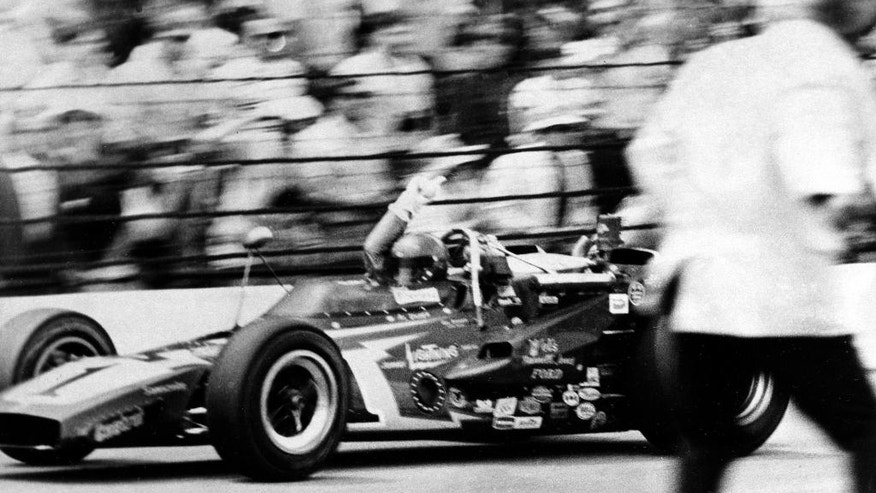 FILE - In this May 29, 1971 file photo, Al Unser gestures as he takes the checkered flag in his Johnny Lightning Special to win the 55th running of the Indianapolis 500 auto race at Indianapolis Motor Speedway in Indianapolis, Ind. (AP Photo/File)