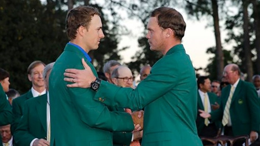Defending champion Jordan Spieth, left, shakes hands with Masters champion Danny Willett, of England, following the final round of the Masters golf tournament Sunday, April 10, 2016, in Augusta, Ga. (AP Photo/David J. Phillip)