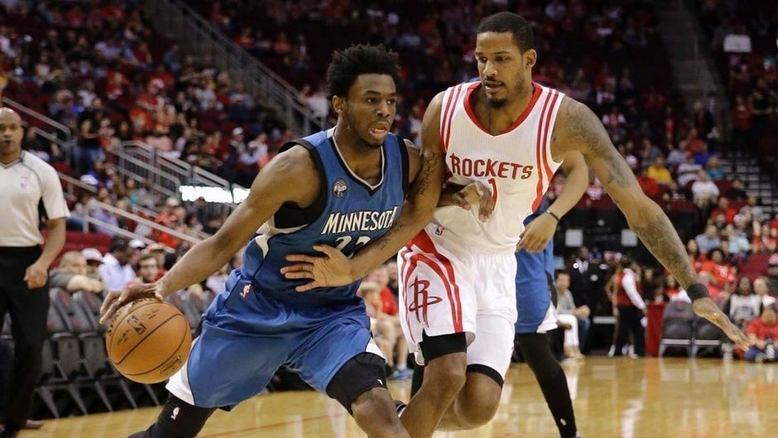 Minnesota Timberwolves' Andrew Wiggins, left, drives toward the basket as Houston Rockets' Trevor Ariza (1) defends during the first half of an NBA basketball game Friday, March 18, 2016, in Houston. (AP Photo/David J. Phillip)