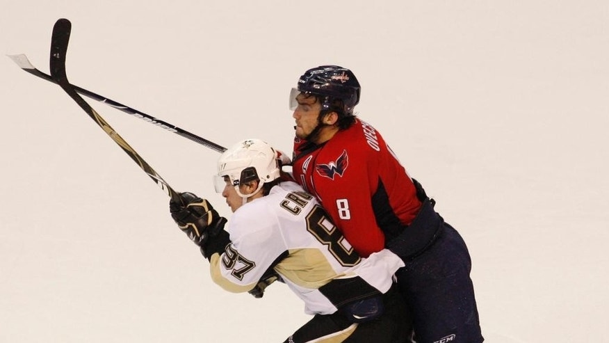 FILE - In this May 2, 2009, file photo, Washington Capitals left wing Alex Ovechkin (8) from Russia collides with Pittsburgh Penguins center Sidney Crosby (87) during the third period of Game 1 of an NHL hockey second-round playoff series in Washington.  Crosby's Penguins and Ovechkin's Capitals are the favorites to come out of the Eastern Conference and could be on a crash course to meet in the playoffs for the first time since 2009. (AP Photo/Pablo Martinez Monsivais, File)