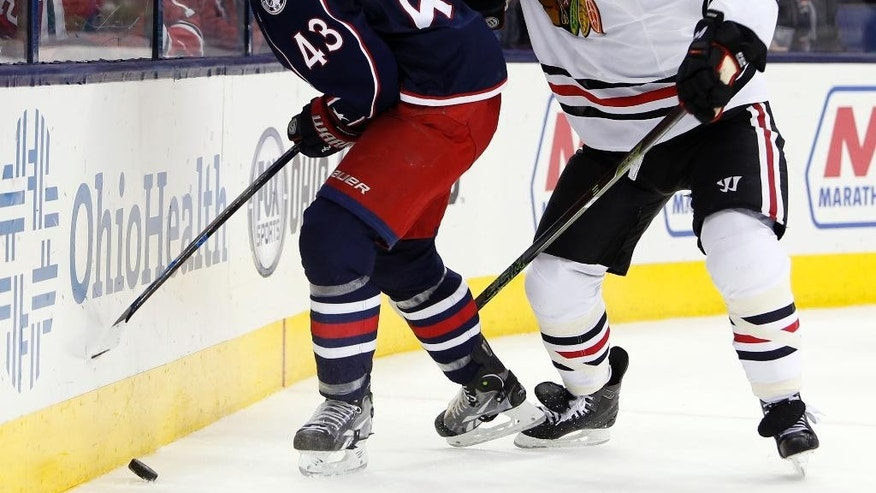Columbus Blue Jackets' Scott Hartnell, left, keeps the puck away from Chicago Blackhawks' Brent Seabrook during the overtime period of an NHL hockey game Saturday, April 9, 2016, in Columbus, Ohio. The Blue Jackets beat the Blackhawks 5-4 in overtime. (AP Photo/Jay LaPrete)